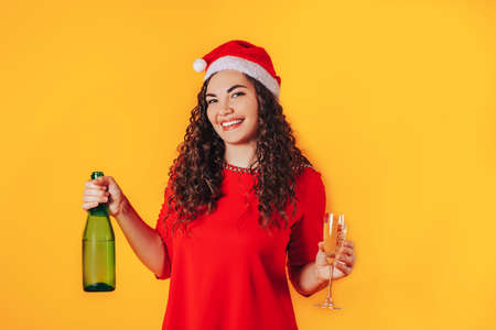 Young beautiful woman on yellow background, on her head she has santa hat. Woman holding bottle and glass in her hands. Christmas mood. Place for text. 版權商用圖片