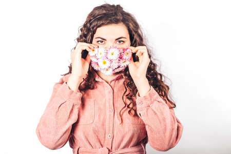 Young beautiful woman in pink suit on white background. She wears protective mask of blooming flowers on her face. Breathe fresh air. Contaminated air.