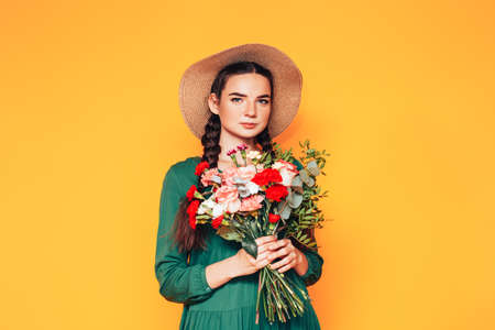 Woman holding a large bouquet of flowers in a green dress on a yellow background Imagens