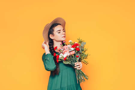 Woman holding a large bouquet of flowers in a green dress on a yellow background. Imagens
