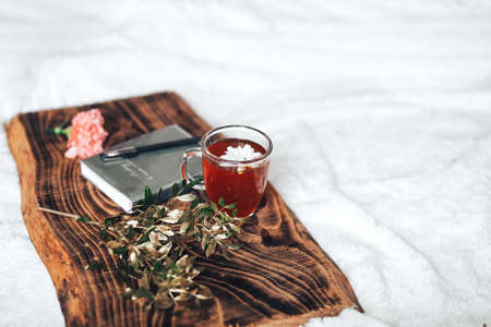 On a wooden tray are a cup of tea, a flower and a notebook with a pen.