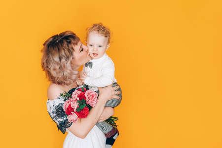 拿着她的胳膊的礼服的妇女小男孩和拿着花美丽的花束在反对黄色背景。节日礼物。