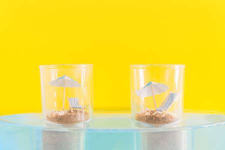 Summer vacation concept during pandemic. Social distance of people on the beach. Two glasses with sand, chaise longue and beach umbrella standing in the water. Banque d'images