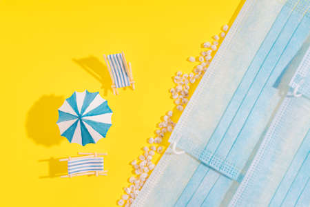 Summer vacation concept during pandemic. Medical masks are depicted as sea and yellow background as sand. Two sun loungers, an umbrella and small seashells standing on yellow background.