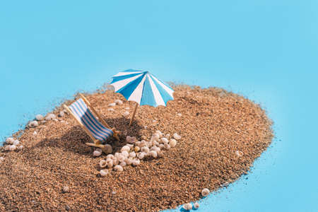Summer vacation concept during pandemic. Slide of sand on blue background like the sea. Deck chair, umbrella and small seashells on the sand.