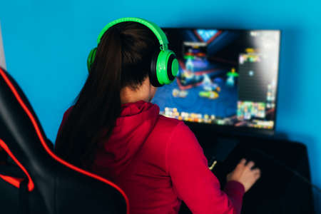 The gamer sits on a gaming chair and plays computer games. The player has green headphones on his head. Banque d'images