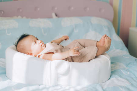 Asian child lying on the bed. Caring for newborn children.