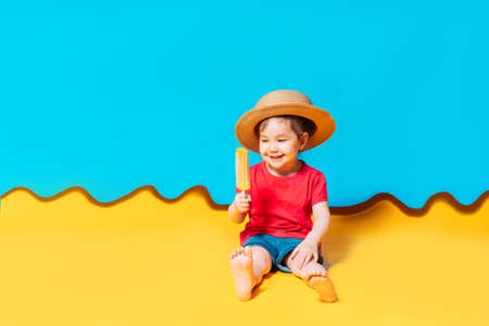 Asian girl in a straw hat licks ice cream. The blue background shows the sky, and the yellow background shows the sand. Banque d'images