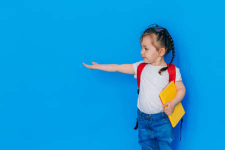 Back to school concept. School girl with red backpack and holding yellow folder in front of blue background. The child stretched out her right hand to the side. Banque d'images