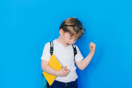 Back to school concept. Schoolboy boy with backpack and holding yellow notebook against blue wall. Child clenched fist showing success.