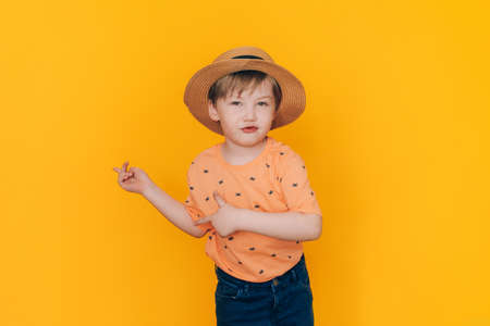 Boy in straw hat shows hands as opposite the yellow background with copyspace. Summer holiday concept.