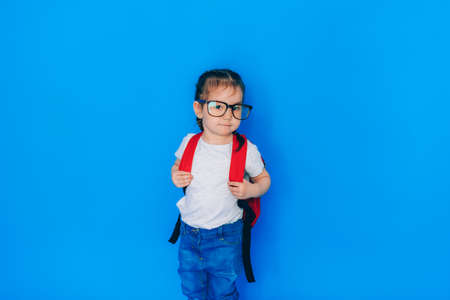 Back to school concept. School girl with red backpack and holding yellow folder in front of blue background.