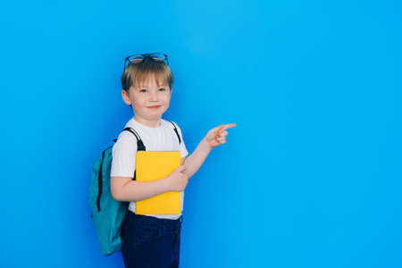 Back to school concept. Schoolboy boy with backpack and holding yellow notebook in front of blue background. Child maintain social distance.