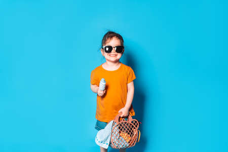 Asian girl in sunglasses licks ice cream. Beach accessories in mesh bag against blue background.