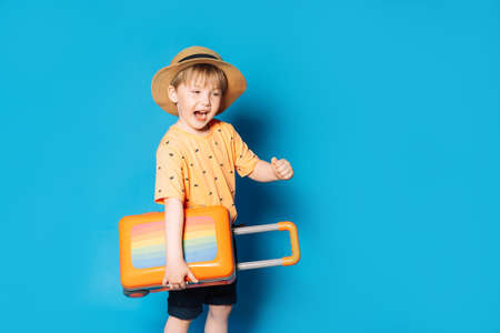 Mixed race boy in hat holding bag against blue background.
