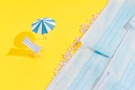 Summer vacation concept during pandemic. Social distance of people on beach. On yellow background, there are seashells and standing chazlongue and an umbrella from sun. Medical masks are depicted as sea. Banque d'images