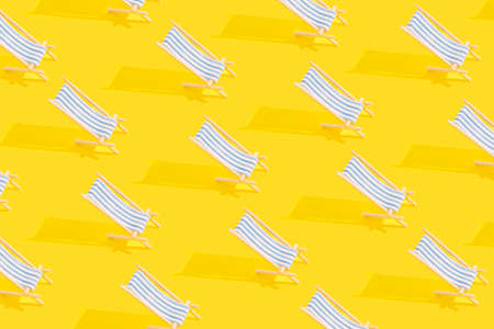 Summer pattern of sun loungers with bright sunlight on yellow background. Vacation concept.
