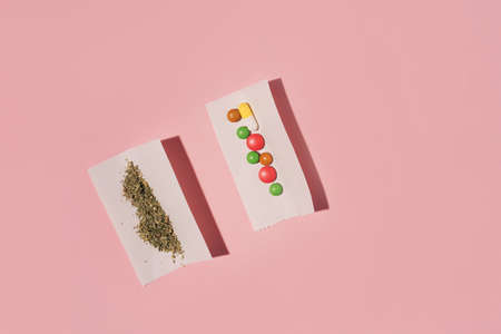 Two paper rolls with dry Marijuana and color pills, flat lay on pink background.