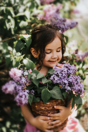 Little girl holding basket with blooming lilacs.