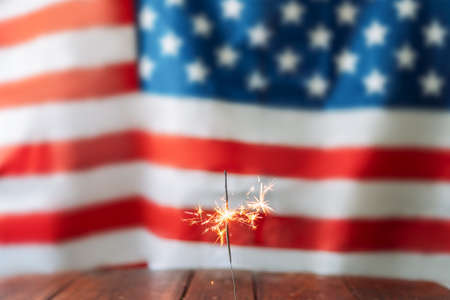 Bengal fire on wooden table in front of the blurred american flag background.