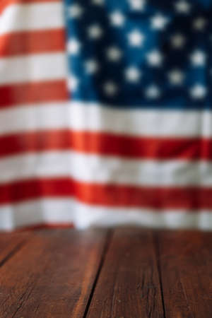 Vertical photo of an empty wooden table in front of the blurred American flag. Independence day concept.