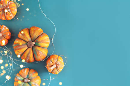Top view of orange pumpkins for halloween with garland on blue background.