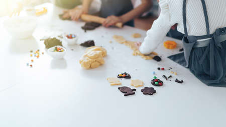 Children prepare cookies with sweets, a boy rolls out the dough with a rolling pin. Leisure activity with children concept. Banque d'images
