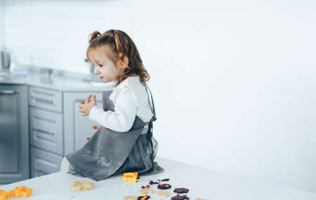 Little girl cooking sweet cookies, sitting on table.