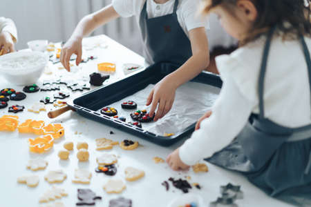 Kids put cookies on baking sheet, hand made cookies. Banque d'images