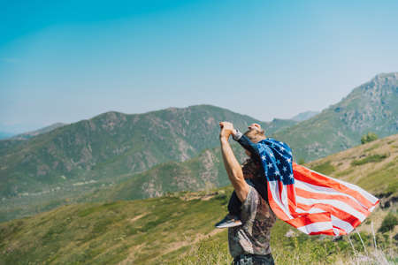 Man and child celebrate fourth of july with american flag in nature.