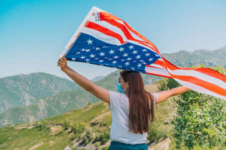 Girl in medical mask holding an American flag in her hands. Celebrate the fourth of July during pandemic.