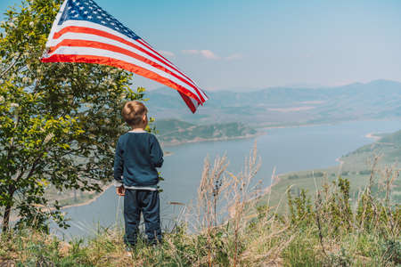 Little boy with American flag looks into the distance at nature. 4th of july Banque d'images