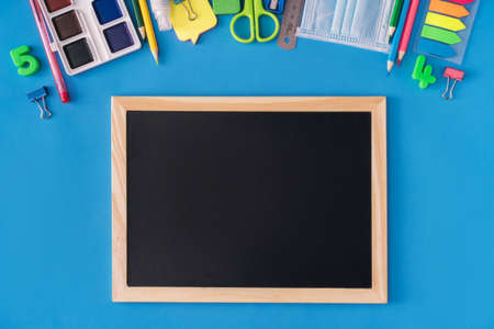 Black school board with school supplies on blue background. Back to school concept. Banque d'images