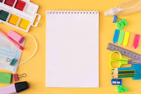 Blank notebook with school supplies, medical mask and paints on yellow background.