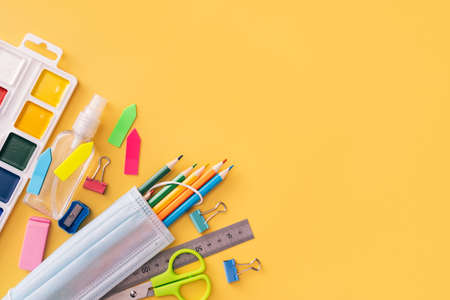 School supplies with paints, medical mask and antiseptic on yellow background. Banque d'images