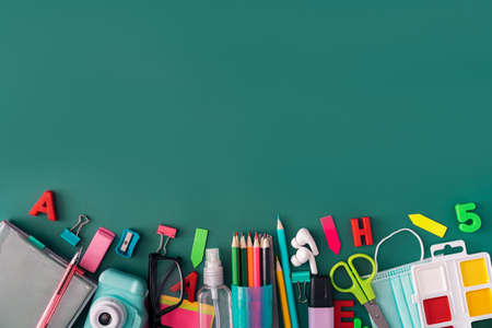 Office stationery with medical mask and headphones on green background.