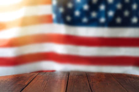 Empty wooden table in front of the blurred American flag. Independence day concept. Banque d'images