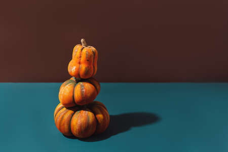 Three handmade pumpkins stand on top of each other against brown and cian background hard shadows.