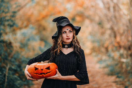 Girl dressed as witch holding pumpkin in her hands on forest background. Banque d'images