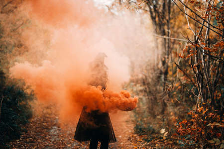 Girl dressed as witch in orange smoke on forest background.