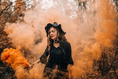 Girl dressed as witch holding smoke bomb in her hands on forest background.
