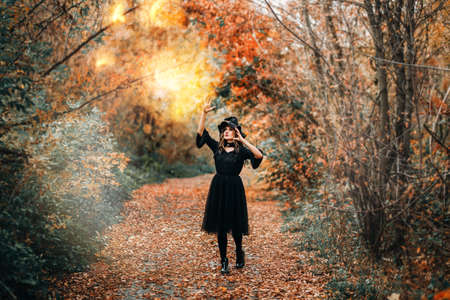 Girl dressed as witch casts fire spell in front of the forest. Banque d'images