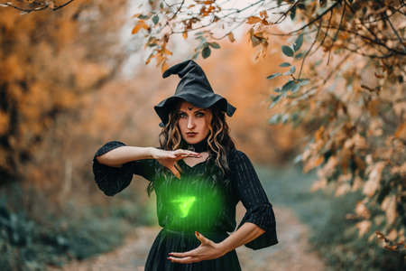 Girl dressed as witch casts spell in the form of green triangle in front of the forest. Banque d'images