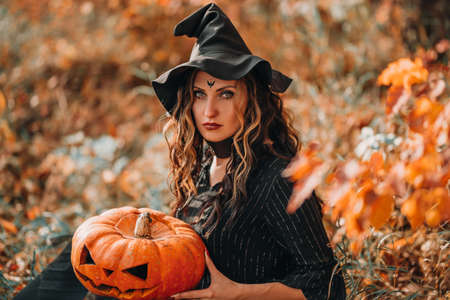 Sitting girl dressed as witch holding pumpkin in the forest.