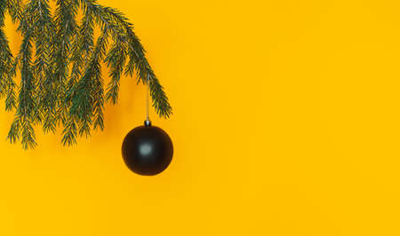 Black matte balls on christmas tree branch against a yellow background. Banque d'images