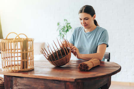 Woman weaves basket of paper tubes on wooden table.