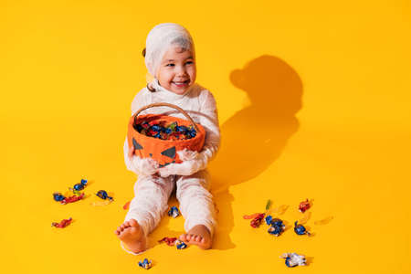 Child in mummy costume holds basket in the form of pumpkin with sweets in his hands.