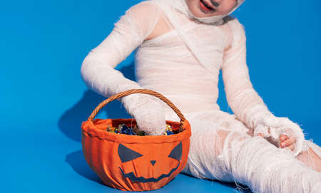 Child in mummy costume eats candies from basket in the form of pumpkin against blue background. Halloween trick or treat