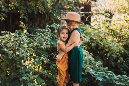 Brother and sister hugging in garden, green and yellow gardener overals, happy family.