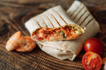 Shawarma cut in half with shrimps and tomato on wooden table. Banque d'images
